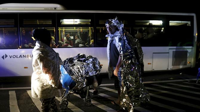Migrants stand next to buses bound for Austria and Germany, along the M1 highway near Budapest, Hungary