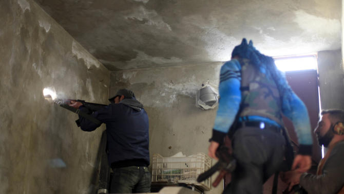 A Syrian fighter shoots his weapon through a hole in the wall during clashes with Syrian army forces in the town of Harem on the outskirts of Idlib, Syria, Saturday, Nov. 17, 2012. (AP Photo/ Khalil Hamra)