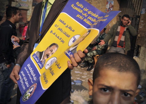 An Egyptian party activist holds an election banner outside a polling station in Cairo, Egypt, Tuesday, Nov. 29, 2011. Polls opened Tuesday for a second day of voting in Egypt's landmark parliamentary elections, the first since Hosni Mubarak's ouster in a popular uprising earlier this year. (AP Photo/Bela Szandelszky)