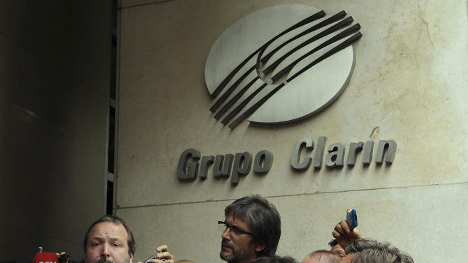 ** CORRECTS SPELLING OF SECOND REFERENCE TO SABBATELLA INSTEAD OF SABATELLA ** Martin Sabbatella,  left, head of the government media regulation body, is surrounded by reporters outside the newspaper office of  Grupo Clarin in Buenos Aires, Argentina, Monday, Dec. 17, 2012. Sabbatella said Monday that the government will make the conglomerate and other companies comply with the law, which bars any company from owning too many different media properties. The law could require Grupo Clarin to sell off broadcast licenses as well as its majority stake in Cablevision, the cable TV network that has become the company's cash cow. (AP Photo/Daniel Dabove,Telam)