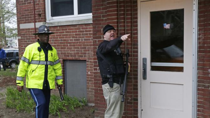 A Department of Homeland Security officer, right, prepares to enter an apartment building while looking for a suspect in the Boston Marathon bombings in Watertown, Mass., Friday, April 19, 2013. The bombs that blew up seconds apart near the finish line of the Boston Marathon left the streets spattered with blood and glass, and gaping questions of who chose to attack and why. (AP Photo/Charles Krupa)