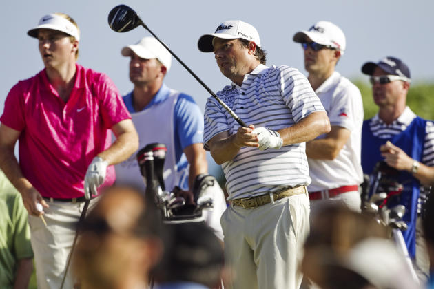 Tim Clark, center, of South Africa, follows his shot off the 14th tee as playing partners Russell Henley, left, and Scott Langley, second from right, watch during the final round of the Sony Open golf