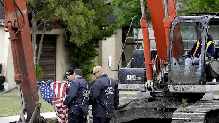 Hillsborough County, Fla., firefighters fold an American flag after removing it from a home is being destroyed Sunday, March 3, 2013, after a sinkhole opened up underneath a bedroom late Thursday evening and swallowed a man in Seffner, Fla. (AP Photo/Chris O'Meara)