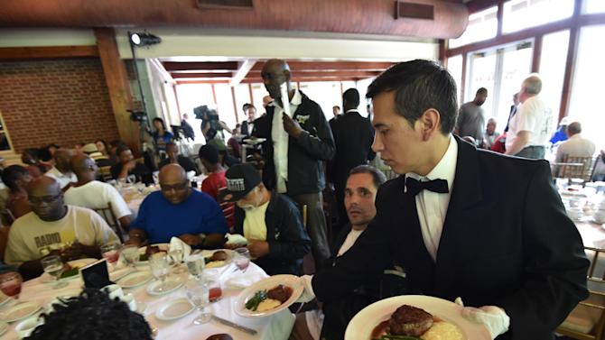 A waiter serves meals as Chinese philanthropist Chen Guangbiao hosts a lunch for 250 homeless people on June 25, 2014 at The Boathouse restaurant in New York's Central Park