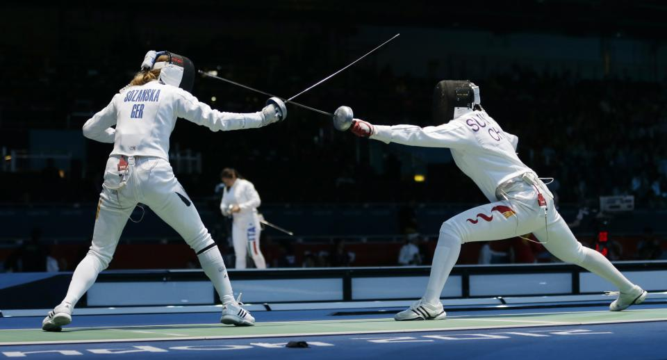 Germany's Monika Sozanska, left, competes against China's Sun Yujie during their match in women's team epee fencing at the 2012 Summer Olympics, Saturday, Aug. 4, 2012, in London. (AP Photo/Hassan Ammar)