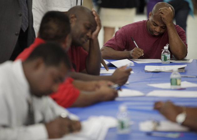 In this Tuesday, Aug. 21, 2012, photo, job seekers fill out applications at a construction job fair in New York. The number of Americans seeking unemployment benefits was unchanged last week at a seasonally adjusted 374,000, suggesting slow improvement in the job market. The Labor Department said Thursday, Aug. 30, 2012 that the four-week moving average, a less volatile measure, increased to 370,250.(AP Photo/Seth Wenig)