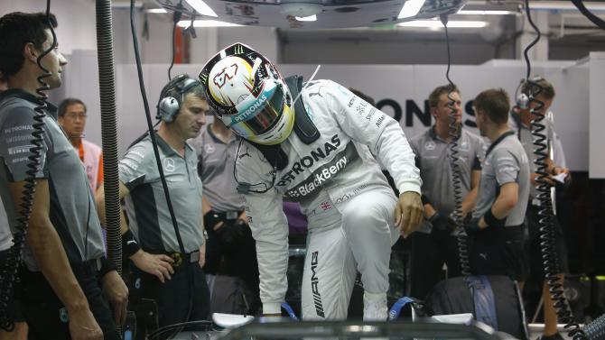 Mercedes Formula One driver Lewis Hamilton of Britain climbs into his car during the second practice session of the Singapore F1 Grand Prix at the Marina Bay street circuit in Singapore
