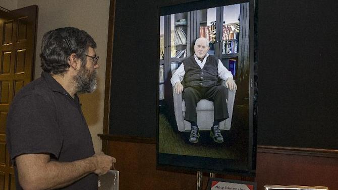 "In this photo taken Tuesday, Jan. 29, 2013, University of Southern California Institute for Creative Technologies, computer scientist David Traum, left, interacts with Holocaust survivor, Pinchas Gutter, seen on a ""Virtual Survivor Visualization,"" at the USC campus in Los Angeles. A collaboration with the Shoah Foundation is digitizing aging Holocaust survivors to create three-dimensional holograms that would not only be able to tell their stories to future generations but to engage in dialogue with them. (AP Photo/Damian Dovarganes)"