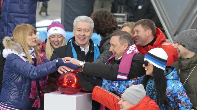 Moscow's Mayor Sergei Sobyanin, center, surrounded by various sport enthusiasts and entertainers hits a symbolic button to launch the one-year count down clock for the upcoming 2014 Sochi Olympics in Moscow, Russia, Thursday, Feb. 7, 2013. (AP Photo/Mikhail Metzel)