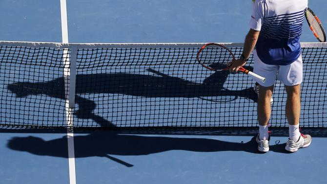 The shadows of Kei Nishikori (top) of Japan and Stan Wawrinka of Switzerland are seen as they shake hands after Nishikori was defeated in their men's singles quarter-final match at the Australian Open 2015 tennis tournament in Melbourne