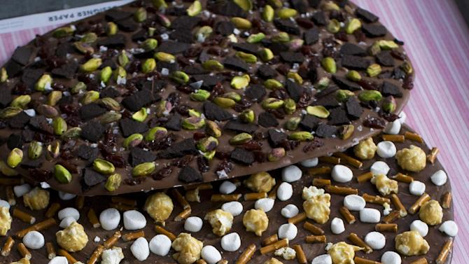In this image taken on Jan. 21, 2013, four variations of Valentine's Day chocolate bark are shown in Concord, N.H. You can top the chocolate with whatever your love loves. (AP Photo/Matthew Mead)