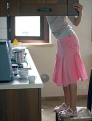 girl looking in kitchen cabinet