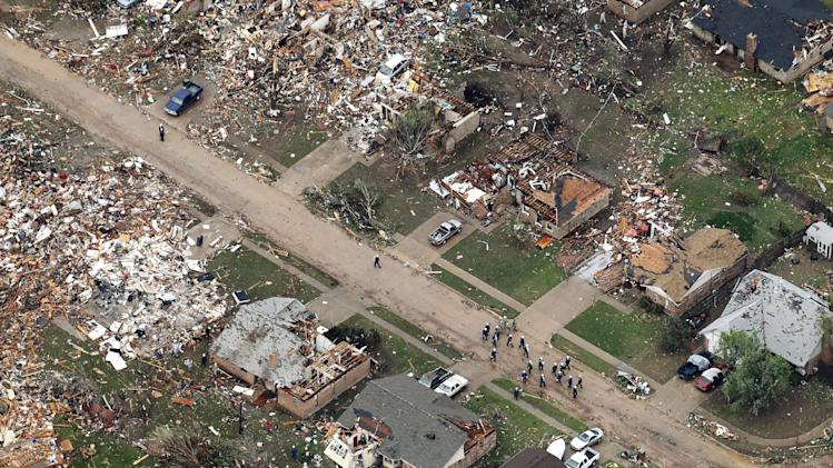 In this Tuesday, May 21, 2013 aerial photo, emergency responders make their way down a street of damaged homes following Monday's tornado in Moore, Oklahoma. (AP Photo/Kim Johnson Flodin)