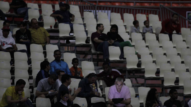 A fan looks at his laptop as he waits for play to resume at a FIBA World Cup qualifying basketball game, during a power outage, in Caracas,Venezuela, Tuesday, Sept. 3, 2013. A power outage hit nearly half of Venezuela, including much of Caracas, which normally escapes blackouts. Authorities say delays in several initiatives designed to boost electricity output are partly to blame. But they also have suggested that government foes have sabotaged the grid. (AP Photo/Ariana Cubillos)