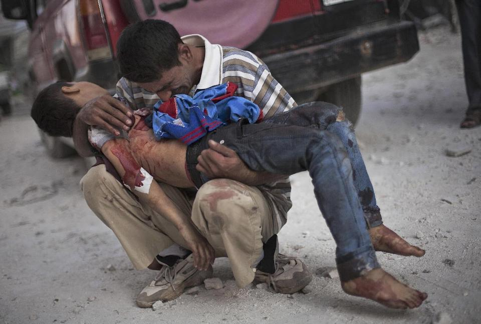 FOR USE AS DESIRED, YEAR END PHOTOS - FILE - In this Oct. 3, 2012 file photo, a Syrian man cries while holding the body of his son killed by the Syrian Army near Dar El Shifa hospital in Aleppo, Syria. (AP Photo/ Manu Brabo, File)