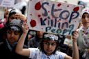 A protester holds up a sign during a demonstration outside the Syrian embassy in London