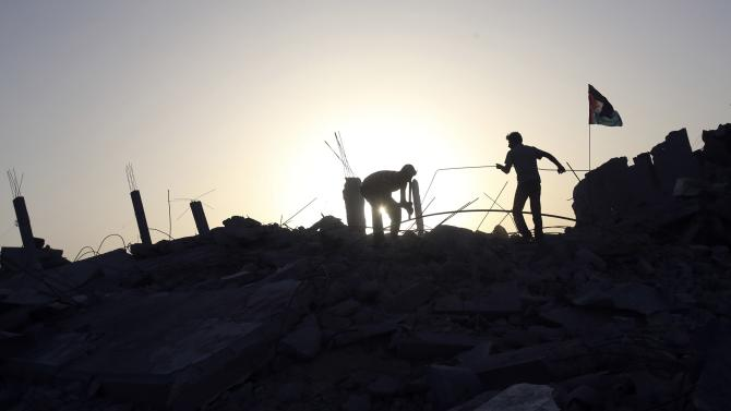 Palestinian men remove debris as they search for belongings in the rubble of a house, which witnesses said was destroyed during the seven-week Israeli offensive in Khan Younis in the southern Gaza Strip