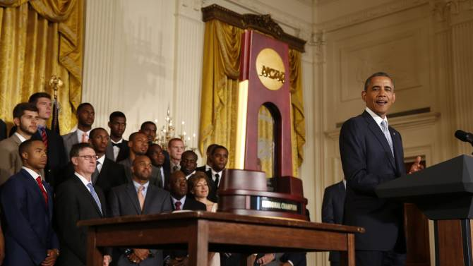 U.S. President Obama looks at the trophy as he honors team members of the 2014 NCAA champion UConn Huskies men's and women's basketball teams in Washington