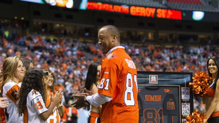 Former B.C Lions Geroy Simon reacts while his number is retired during a half-time celebration at the team's CFL football game against the Winnipeg Blue Bombers in Vancouver