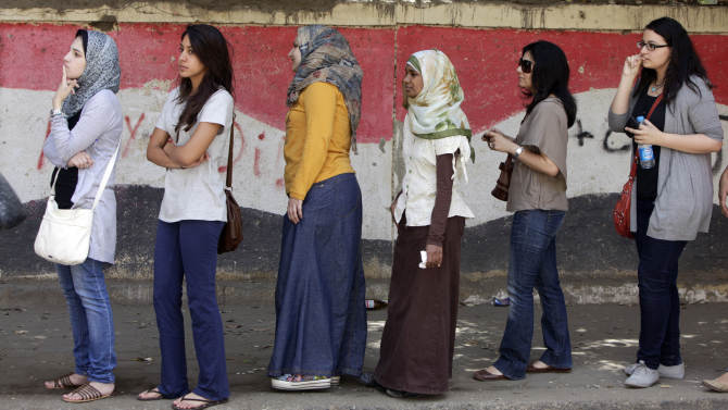 Egyptian women line up outside a polling station in Cairo, Egypt, Thursday, May 24, 2012. In a wide-open race that will define the nation's future political course, Egyptians voted Thursday on the second day of a landmark presidential election that will produce a successor to longtime authoritarian ruler Hosni Mubarak. The Egyptian flag is painted at background. (AP Photo/Amr Nabil)