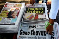 A woman walks arrages heaps of newspapers in Caracas announcing the win by President Hugo Chavez