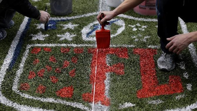 Works paint an NFL logo Tuesday, Jan. 14, 2014, as they prepare CenturyLink Field in Seattle for Sunday's NFL football NFC championship game between the Seattle Seahawks and the San Francisco 49ers