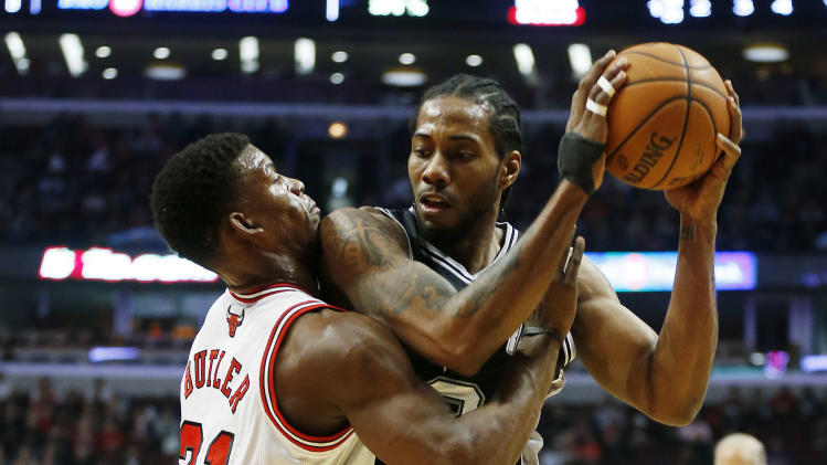 Chicago Bulls shooting guard Jimmy Butler (21) guards San Antonio Spurs small forward Kawhi Leonard (2) during the first half of an NBA basketball game on Tuesday, March 11, 2014, in Chicago. (AP Photo/Andrew A. Nelles)