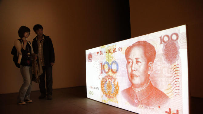 """In this photo taken Thursday, April 8, 2010, visitors look at the art work by American artist Tony Oursler entitled """"100 Yuan (People's Republic of China)"""" which features a projection of a Chinese renminbi note with a talking Mao Zedong at a gallery in Beijing, China. China's yuan has joined the ranks of the most traded currencies for the first time, underlining the growing might of the world's second-largest economy. The yuan became one of the top 10 traded currencies in 2013, rising to No. 9 on the list due to a """"significant expansion"""" in offshore trading, the Bank for International Settlements said in a report Thursday, Sep 5, 2013. (AP Photo/Ng Han Guan)"""