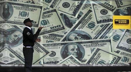A security guard walks past a montage of old U.S. dollar bills outside a currency exchange bureau ahead of a scheduled State visit by the U.S. President Barack Obama in Kenya's capital Nairobi