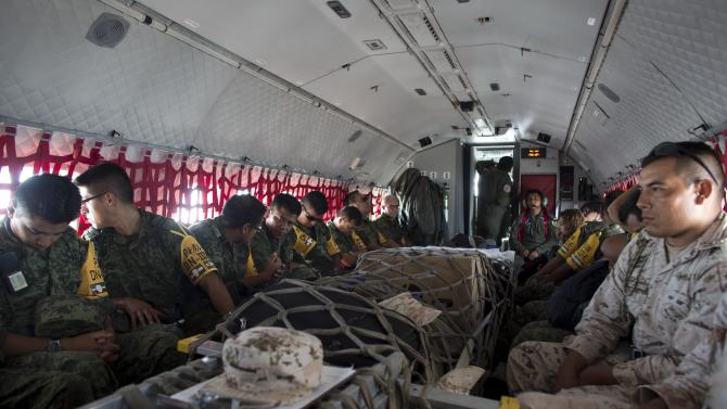 Soldiers sit on a plane loaded with supplies bound for San Jose de los Cabos, at the military airbase in La Paz, Mexico, Wednesday, Sept. 17, 2014. Odile left the resort city of San Jose de los Cabos seriously battered and mostly without power, phone service and running water. (AP Photo/Dario Lopez-Mills)