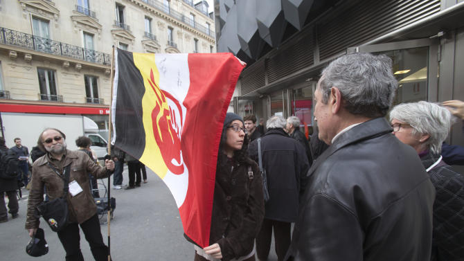 Supporters of the Indian cause hold a flag of the American Indian Movement stand outside of the Druout's auction house to protest the auction of Native American Hopi tribe masks in Paris, Friday, April 12, 2013. A contested auction of dozens of Native American tribal masks went ahead Friday afternoon following a Paris court ruling, in spite of appeals for a delay by the Hopi tribe, its supporters including actor Robert Redford, and the U.S. government. (AP Photo/Michel Euler)