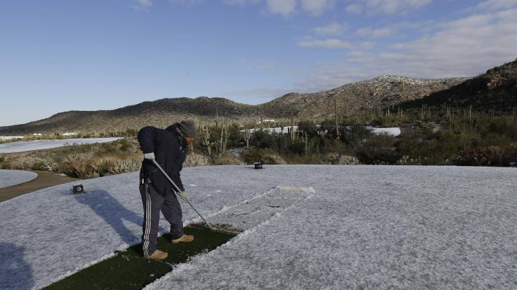Erick Montano uses the back edge of a rake to clear snow off the 10th tee for the Match Play Championship golf tournament, Thursday, Feb. 21, 2013, in Marana, Ariz. A snow storm blanketed the course on Wednesday suspending the first round of play and postponing it until late Thursday morning. (AP Photo/Ted S. Warren)