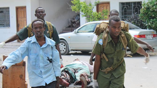 Somali soldiers carry a wounded civilian from the entrance of Mogadishu's court complex after being injured during a siege by militants in Mogadishu, Somalia, Sunday, April 14, 2013. Militants launched a serious and sustained assault on Mogadishu's main court complex Sunday, detonating at least two blasts, taking an unknown number of hostages and exchanging extended volleys of gunfire with government security forces, witnesses said..(AP Photo/Farah Abdi Warsameh)