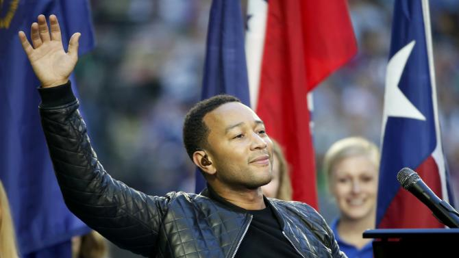 "Singer John Legend waves after performing ""America the Beautiful"" before the start of the NFL Super Bowl XLIX football game between the Seattle Seahawks and the New England Patriots in Glendale"