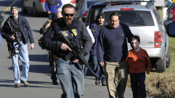 Parents leave a staging area after being reunited with their children following a shooting at the Sandy Hook Elementary School in Newtown, Conn. where authorities say a gunman opened fire, leaving 27 people dead, including 20 children, Friday, Dec. 14, 2012. (AP Photo/Jessica Hill)