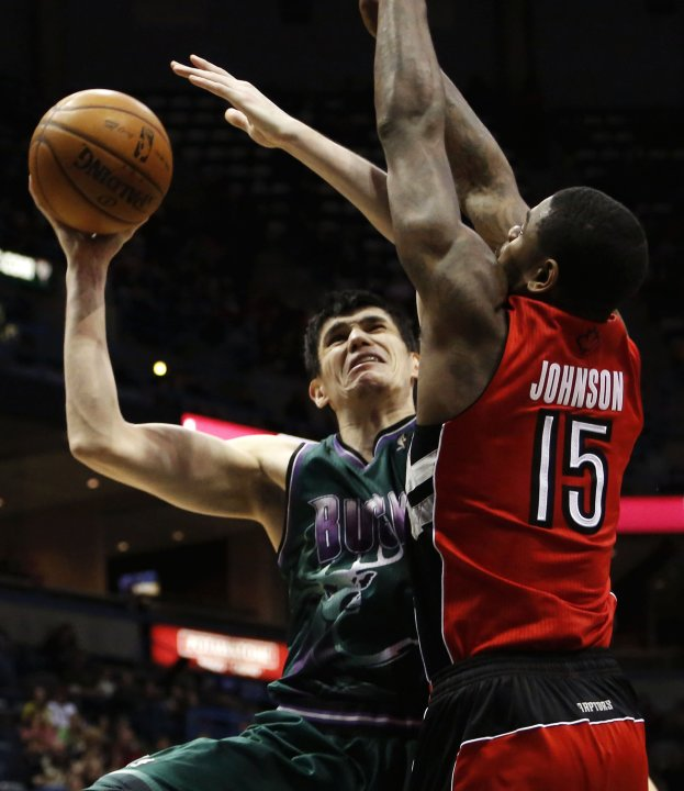 Milwaukee Bucks' Ilyasova drives against Toronto Raptors' Johnson during their NBA basketball game in Milwaukee