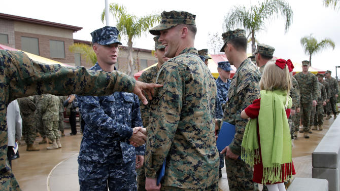 U.S. Marine Sgt. William Soutra Jr., center, is congratulated by fellow service members after receiving the Navy Cross during a ceremony held at Camp Pendleton, Calif., Monday, Dec. 3, 2012. Soutra was awarded the medal for his heroism while serving in Afghanistan. (AP Photo/Jae C. Hong)