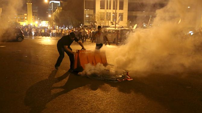 A protester tries to move a tear gas canister fired by security forces in Martyr square, downtown Beirut