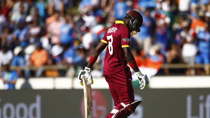 West Indies batsman Jonathan Carter walks off the field after being caught out by India's Mohammed Shami during their Cricket World Cup match in Perth