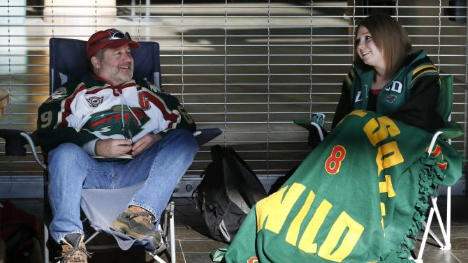FILE - In a Tuesday, Jan. 15, 2013 file photo, Minnesota Wild hockey fans Pat Vos, left, and Jess Crane marked their spots, first and second respectively, for Wild tickets at the Xcel Arena in St. Paul, Minn. The lockout that lasted 119 days has ended, the new collective bargaining agreement is in place and the NHL is finally about to play games again after hastily arranged week-long training camps around the league.  (AP Photo/Jim Mone, File)