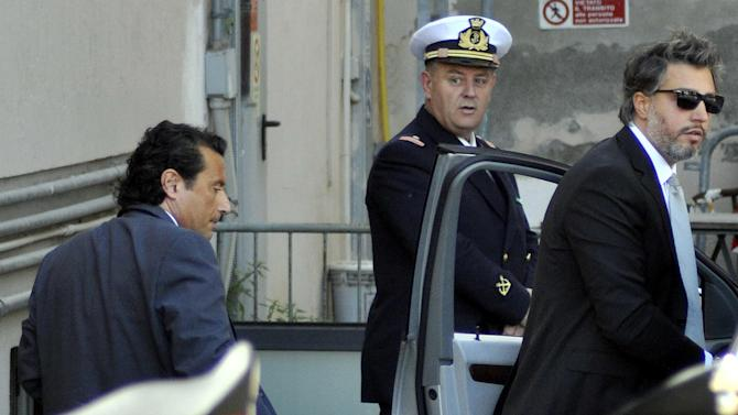 Former captain of the Costa Concordia luxury cruise ship Francesco Schettino, left, arrives with his lawyer Francesco Pepe, right, for a closed-door hearing for the 2012 grounding off Tuscany that killed 32 people, in Grosseto, Italy, Tuesday, May 14, 2013. Prosecutors want Capt. Schettino to stand trial for alleged manslaughter, causing a shipwreck and abandoning the ship before all passengers had been evacuated. (AP Photo/Giacomo Aprili)