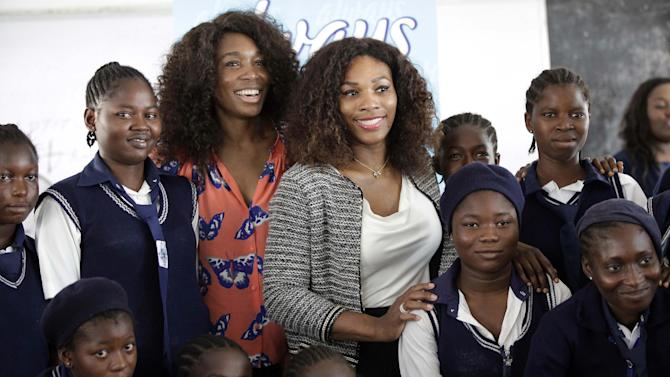 "US tennis players Venus Williams, centre left, and Serena Williams, centre right, pose for a photographs with school girls, during a visit to Lagos, Nigeria, Thursday, Nov. 1, 2012. On their first visit to Nigeria, Serena and Venus Williams want to inspire local kids to set their goals high. We were really able to break the mold and win a lot of Grand Slams and a lot of tournaments and not only that, but kind of change the face of tennis,"" Serena said Wednesday before an exhibition match against her sister in Lagos on Friday. (AP Photo/Sunday Alamba)"