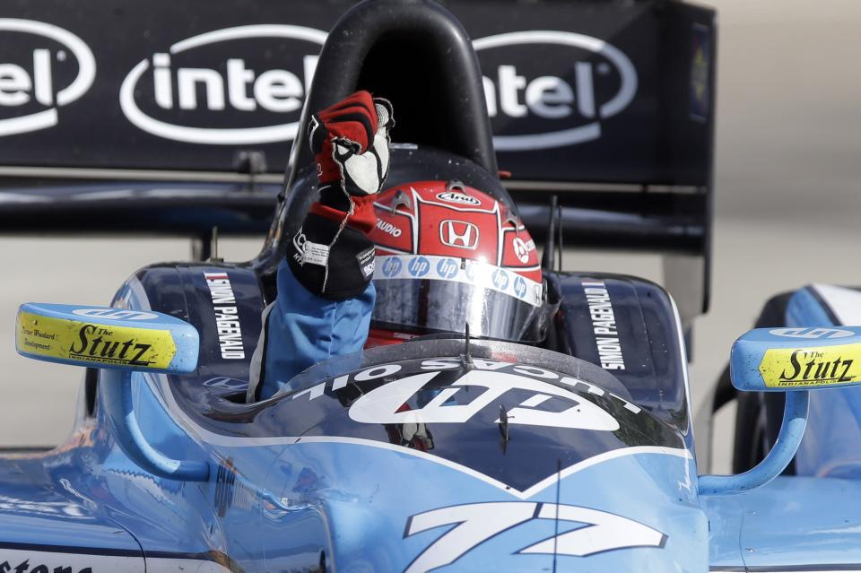 Simon Pagenaud, of France, raises his fist on his victory lap at the IndyCar Detroit Grand Prix auto race on Belle Isle in Detroit, Sunday, June 2, 2013. The victory was Pagenaud's first. (AP Photo/Carlos Osorio)