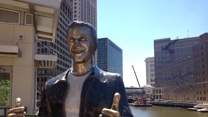 "This June 26, 2012 photo shows ""The Bronze Fonz,"" a statue in the image of the character The Fonz, played by Henry Winkler in the 1970s series ""Happy Days,"" along the Milwaukee Riverwalk.  The riverwalk spans nearly three miles along the Milwaukee River, running from the East Side, through downtown and into the Third Ward neighborhood. (AP Photo/Carr?ie Antlfinger?)"