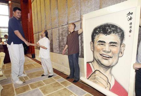 Former NBA basketball player Yao shakes hands with a Chinese artist as he receives a portrait of himself ahead of a charity basketball game organized by Yao Foundation, in Dongguan