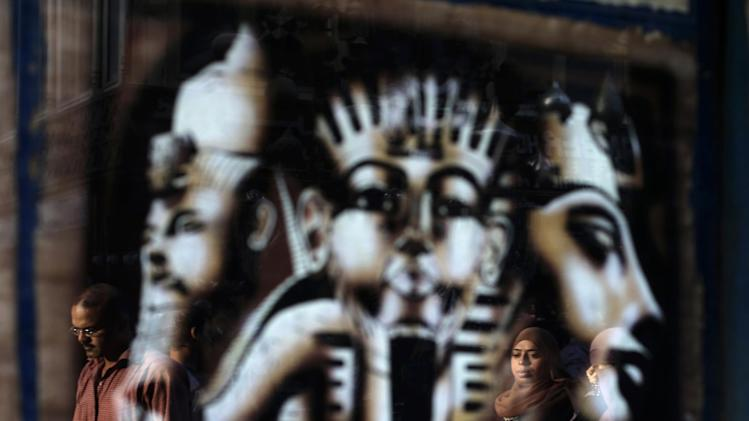 AP10ThingsToSee - Egyptians are reflected in a piece of pharaonic art at the Khan Al-Khalili market, in Cairo, Egypt, Wednesday, May 22, 2013. (AP Photo/Hassan Ammar)