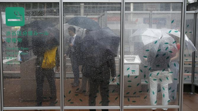 People holding umbrellas smoke cigarettes inside a smoking booth on a street as it rains at Tokyo's Shibuya shopping and amusement district