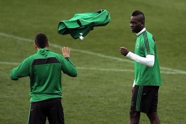 AC Milan's Mario Balotelli, right, throws an item of clothing to his teammate during a training session ahead of Tuesday's Champions League, round of 16, second leg, soccer match against Atlet