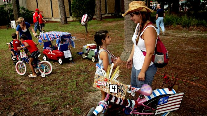 Gabi Hogg, 7, and her mother Jenny Hogg share a moment before mounting a bike for the July Fourth Parade on Highway 77 in Panama City, Fla. Wednesday July 4, 2012. (AP Photo/The News Herald, Andrew P Johnson)