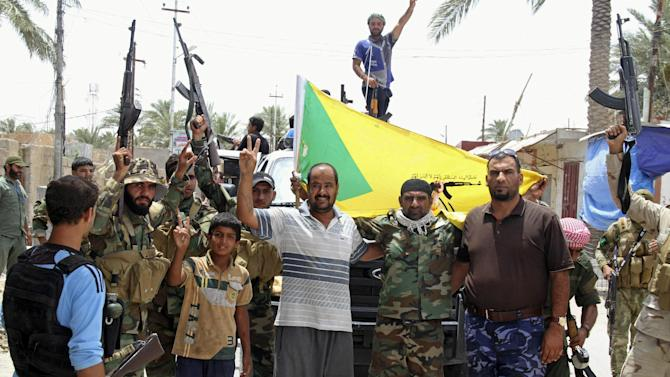 Local residents and Sunni tribal fighters welcome newly-arriving Iraqi Shiite Hezbollah Brigade militiamen,  brandishing their flag, who are joining the fight against Islamic State group militants in Khalidiya, 100 kilometers (60 miles) west of Baghdad, Iraq. (AP Photo)
